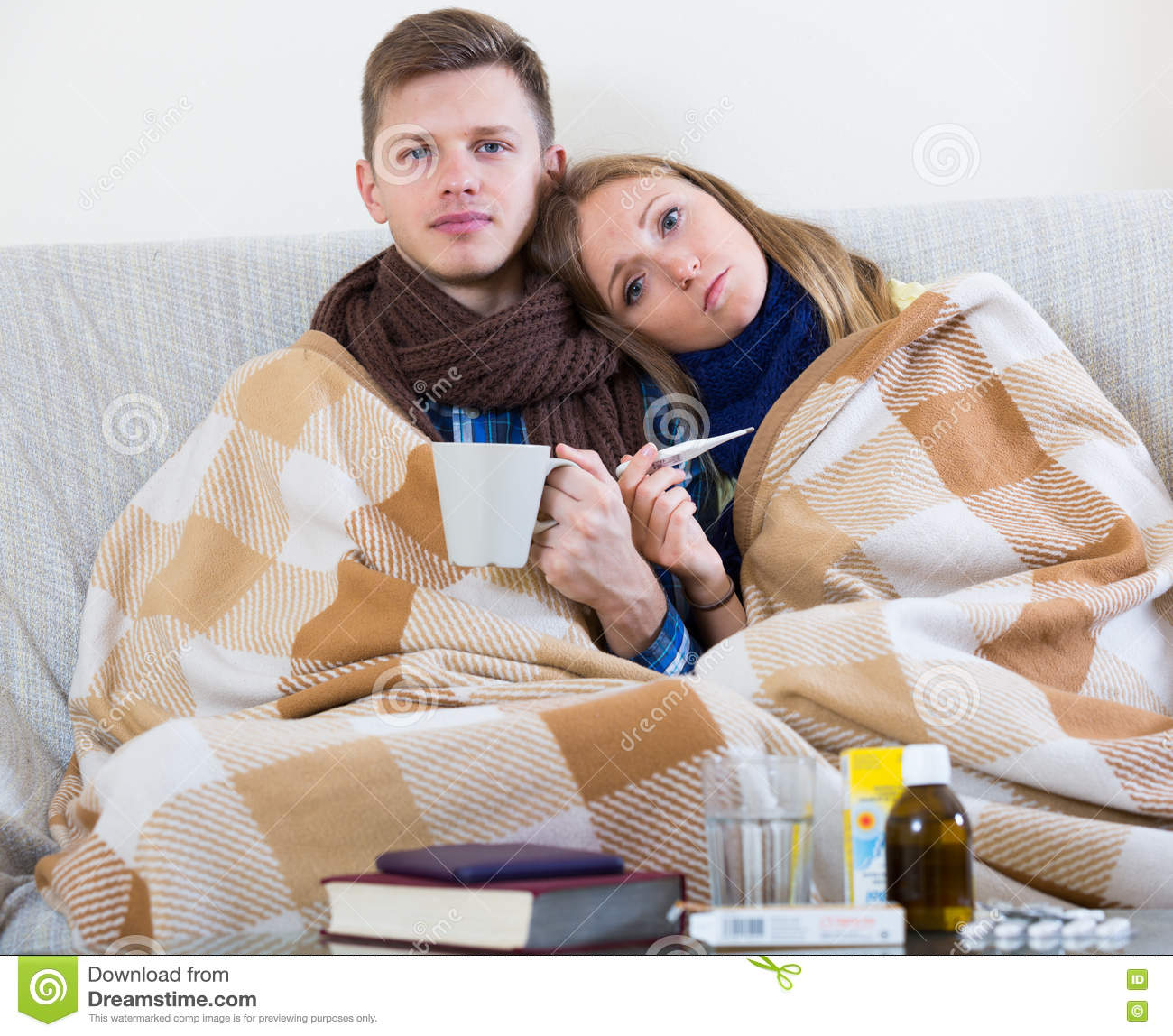 Frozen Couple Sitting On Couch Under Blanket With Thermometer Royalty Free Stock Photo