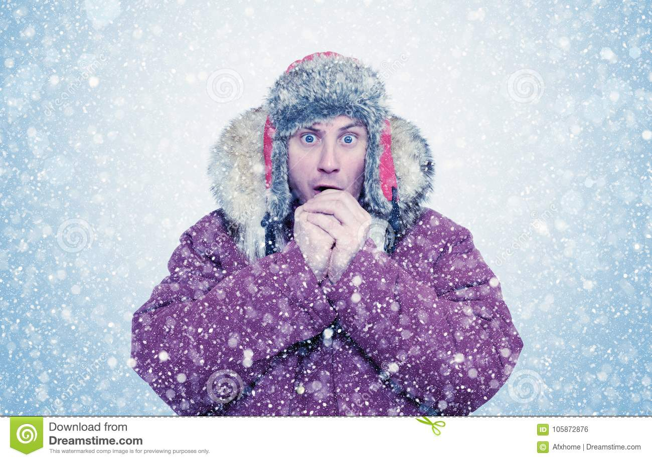 frozen man in winter clothes warming hands cold snow blizzard