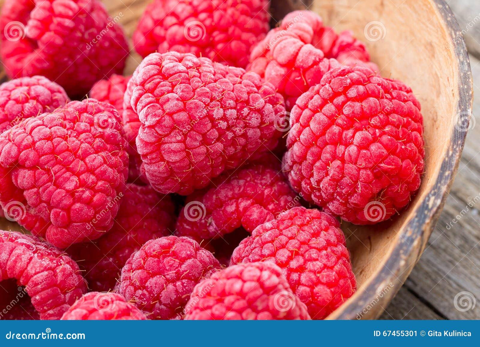 Frozen raspberries on wooden background.
