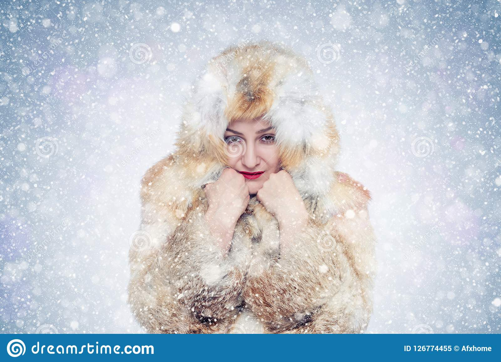 Frozen young woman in a fox fur coat, cold, snow, frost, blizzard