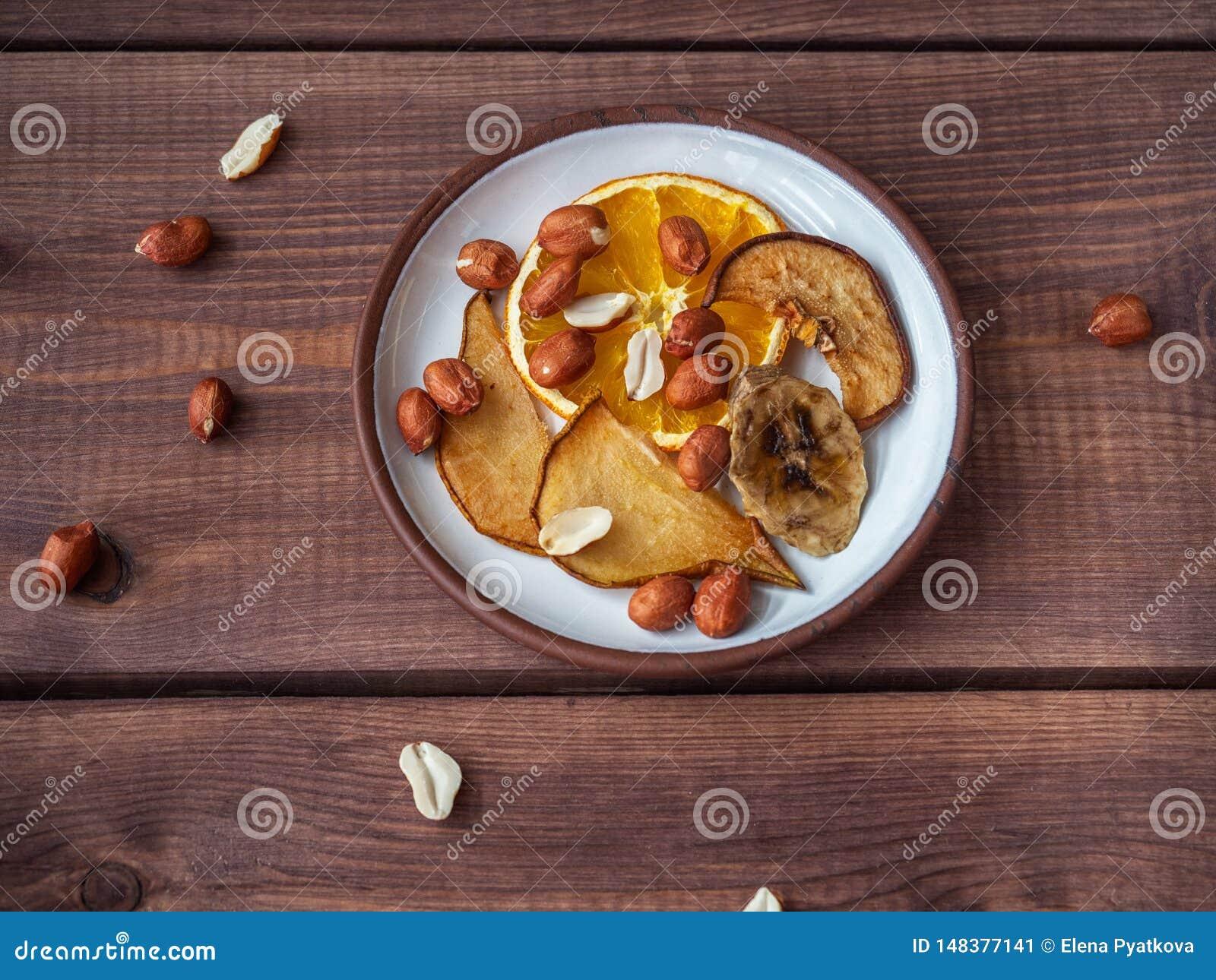 Fruchtchips ohne Zucker und Zus?tze auf einem Pl?ttchen und Erdn?ssen, zerstreut nahe bei der Platte und auf der Platte,