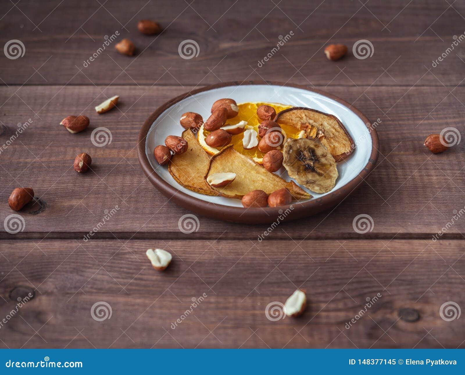 Fruchtchips ohne Zucker und Zus?tze auf einem Pl?ttchen f?r einen gesunden Imbiss f?r die Leute, die einen gesunden Lebensstil f?