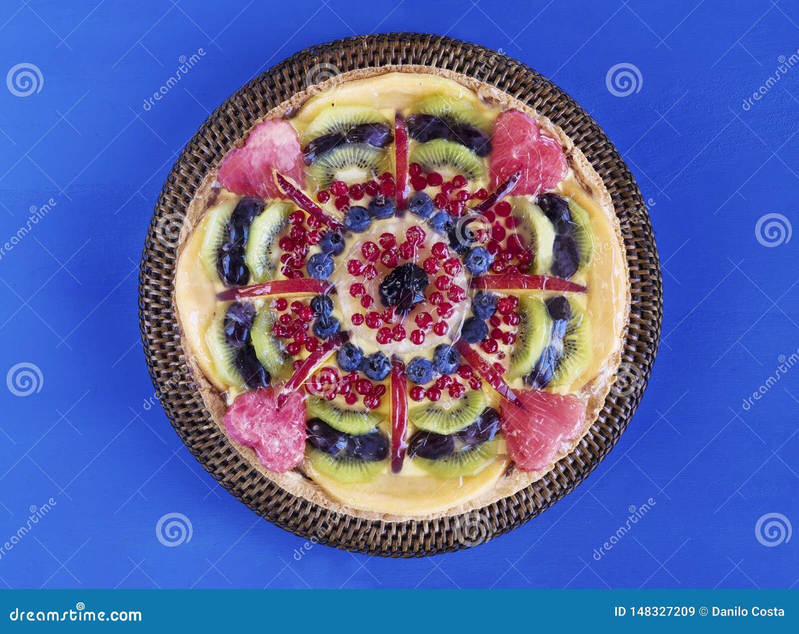 Fruchttörtchen mit Sahne und Beeren auf Kuchenstand, Blumen und Tuch