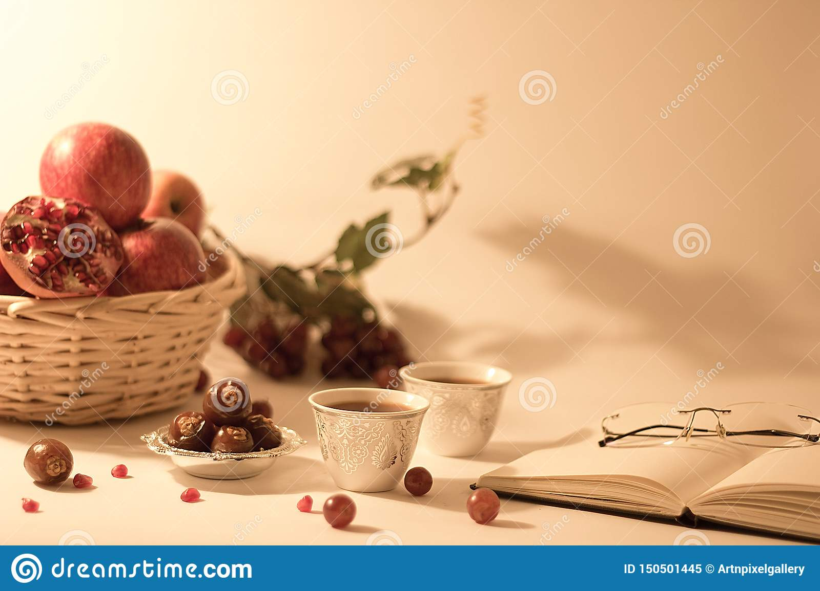 Fruit basket, dates on a silver bowl, arabian tea cups with open book and reading glasses