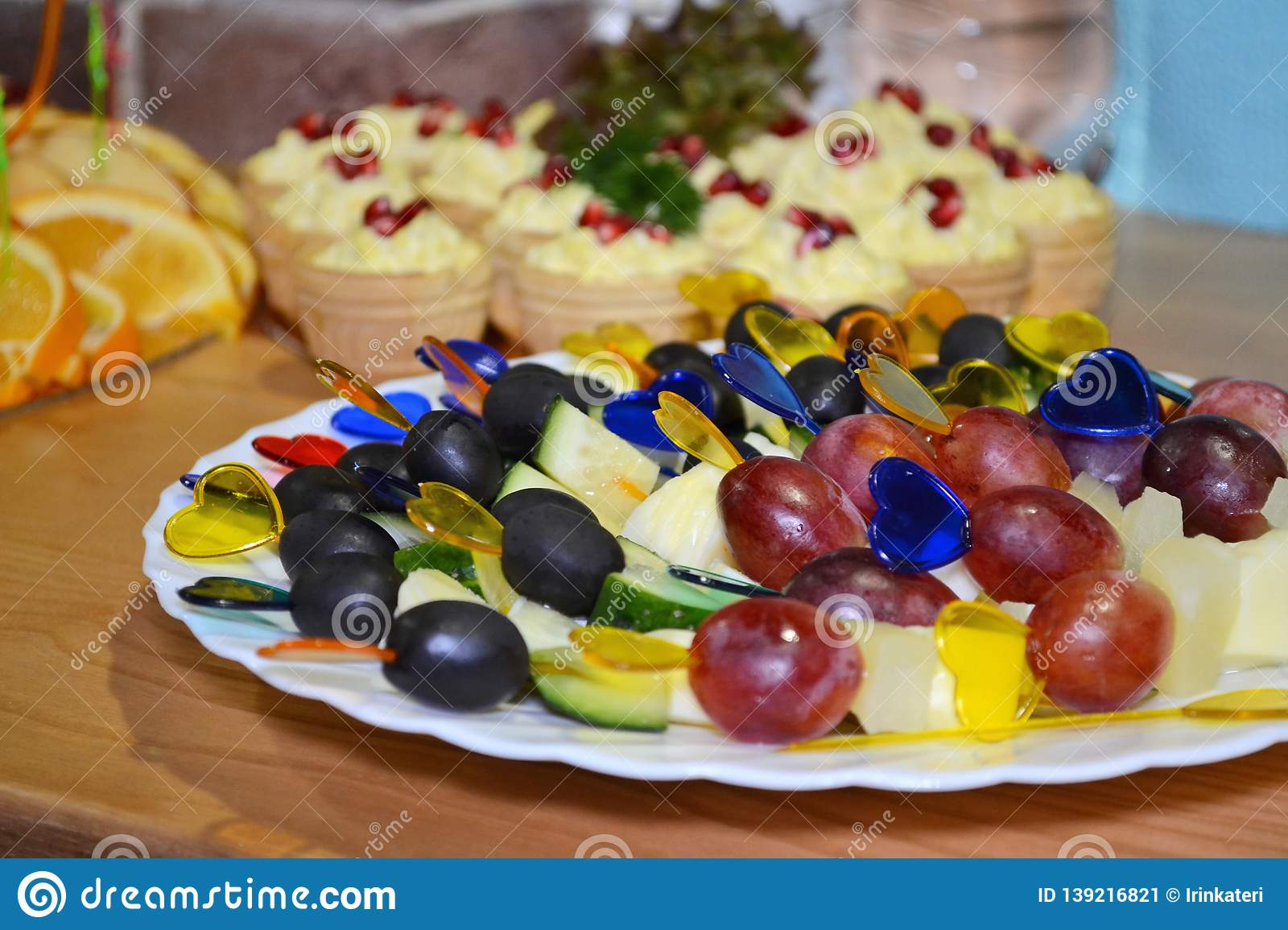 Fruit canape with colored plastic heart skewers on cocktail or a buffet table