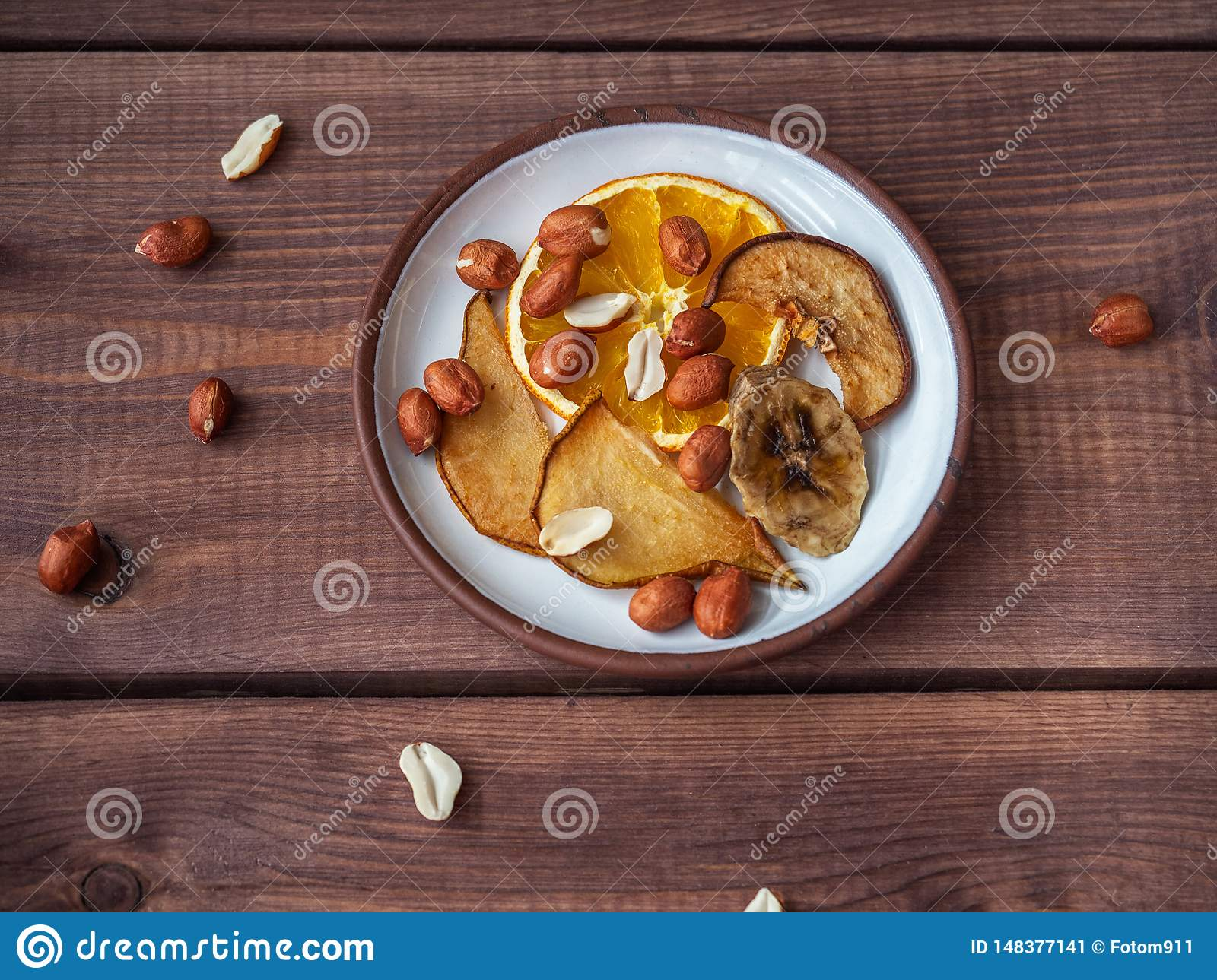 Fruit chips without sugar and additives on a small plate and peanuts, scattered next to the plate and on the plate, the