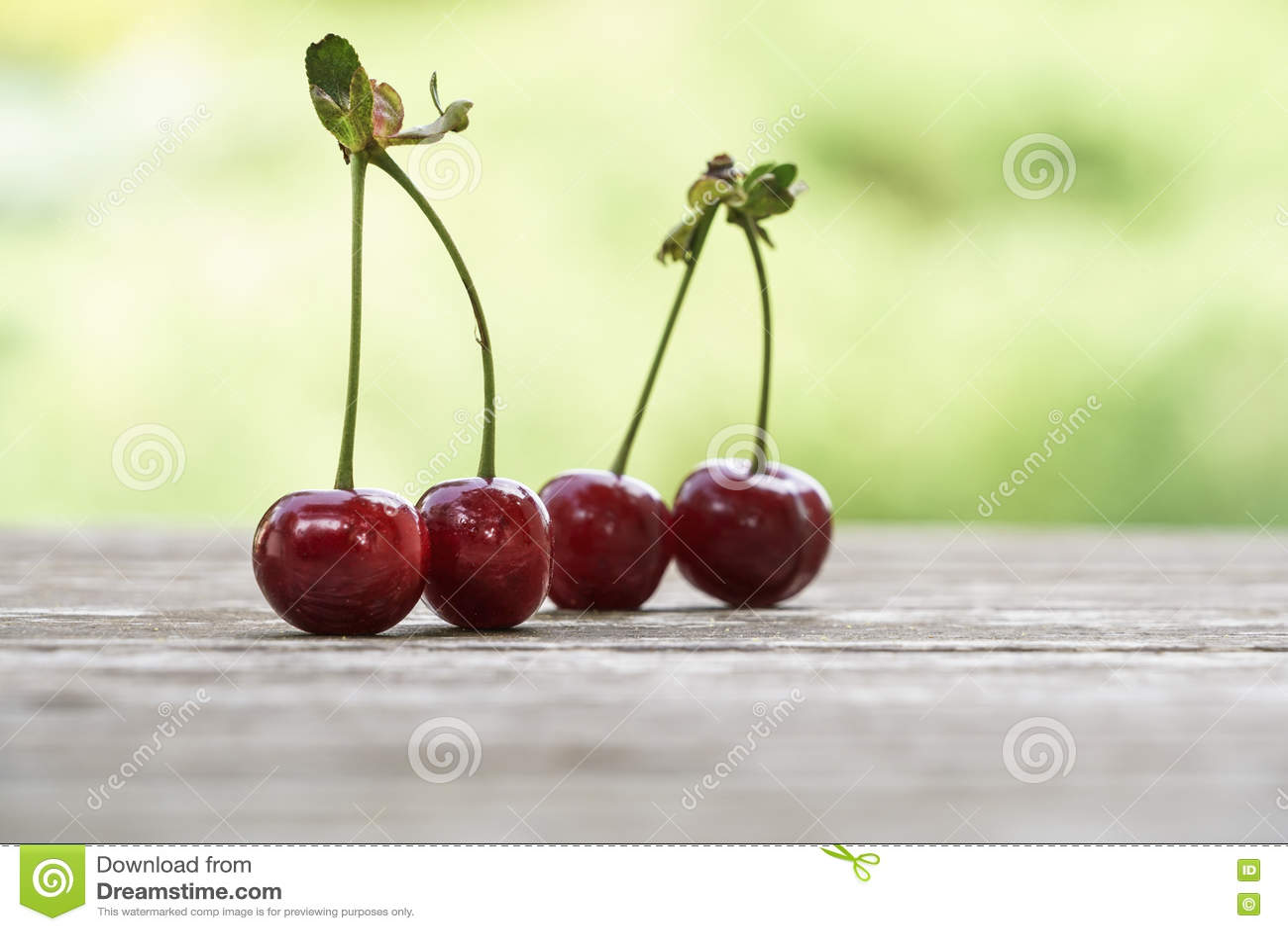Fruit de cerise sur la table en bois au-dessus du fond de vert de bokeh