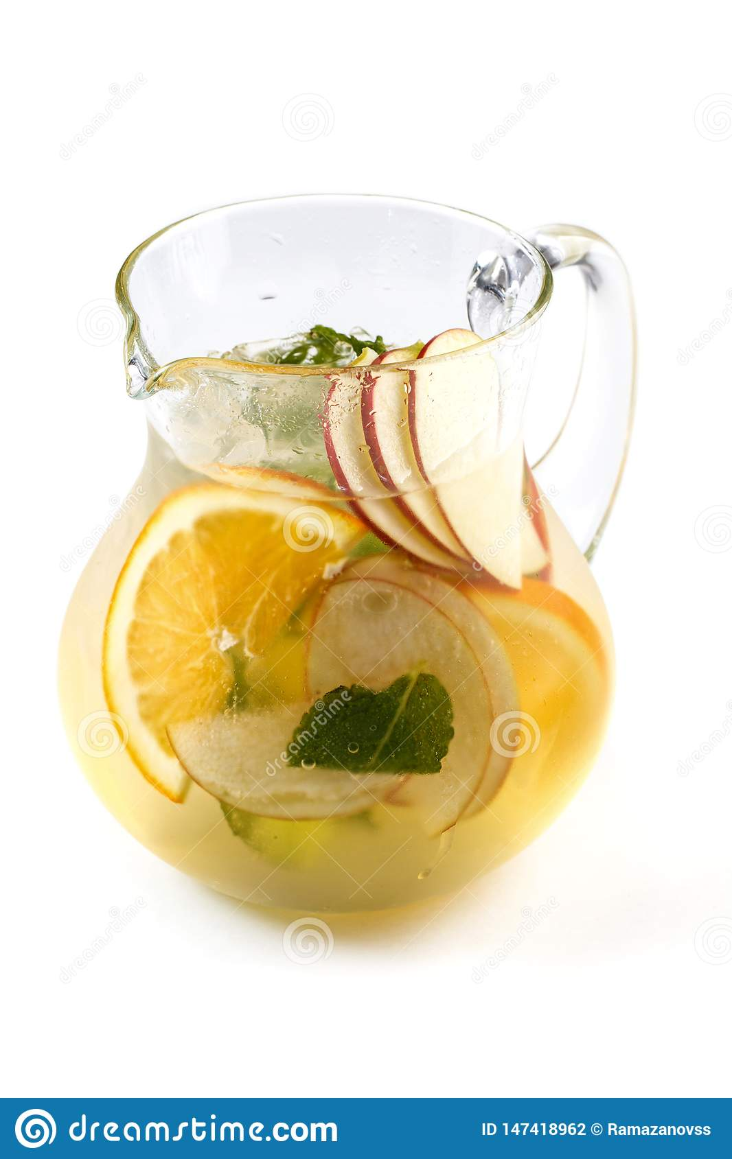 Fruit lemonade with slices of apples and oranges in a jug on an isolated white background