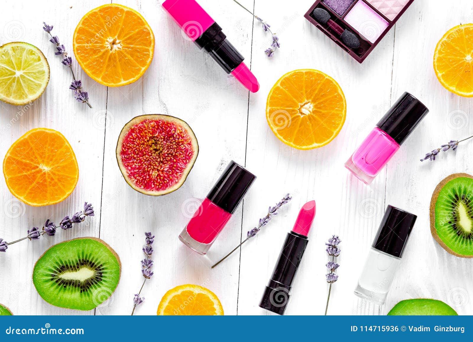 Fruit pattern with lipstick and nailpolish on white desk backgro
