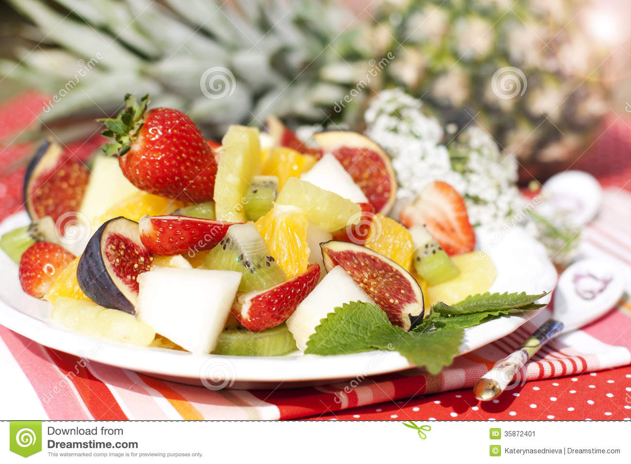 Healthy fruit salad of melon, oranges, figs, strawberries, pineapple ...
