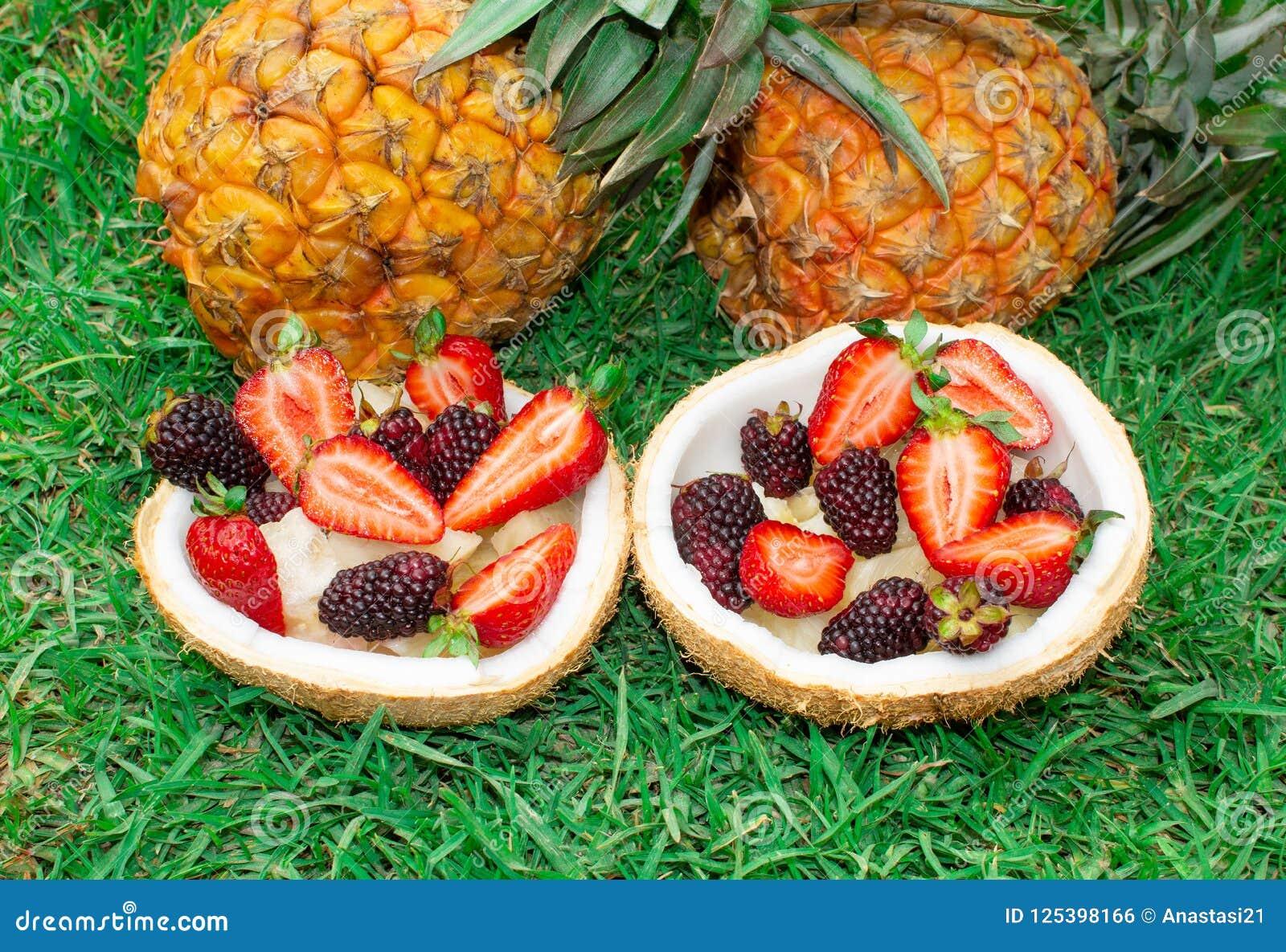 Fruit salad, berries, strawberries, blackberries, ananas in coconut. On the green grass. Still life.