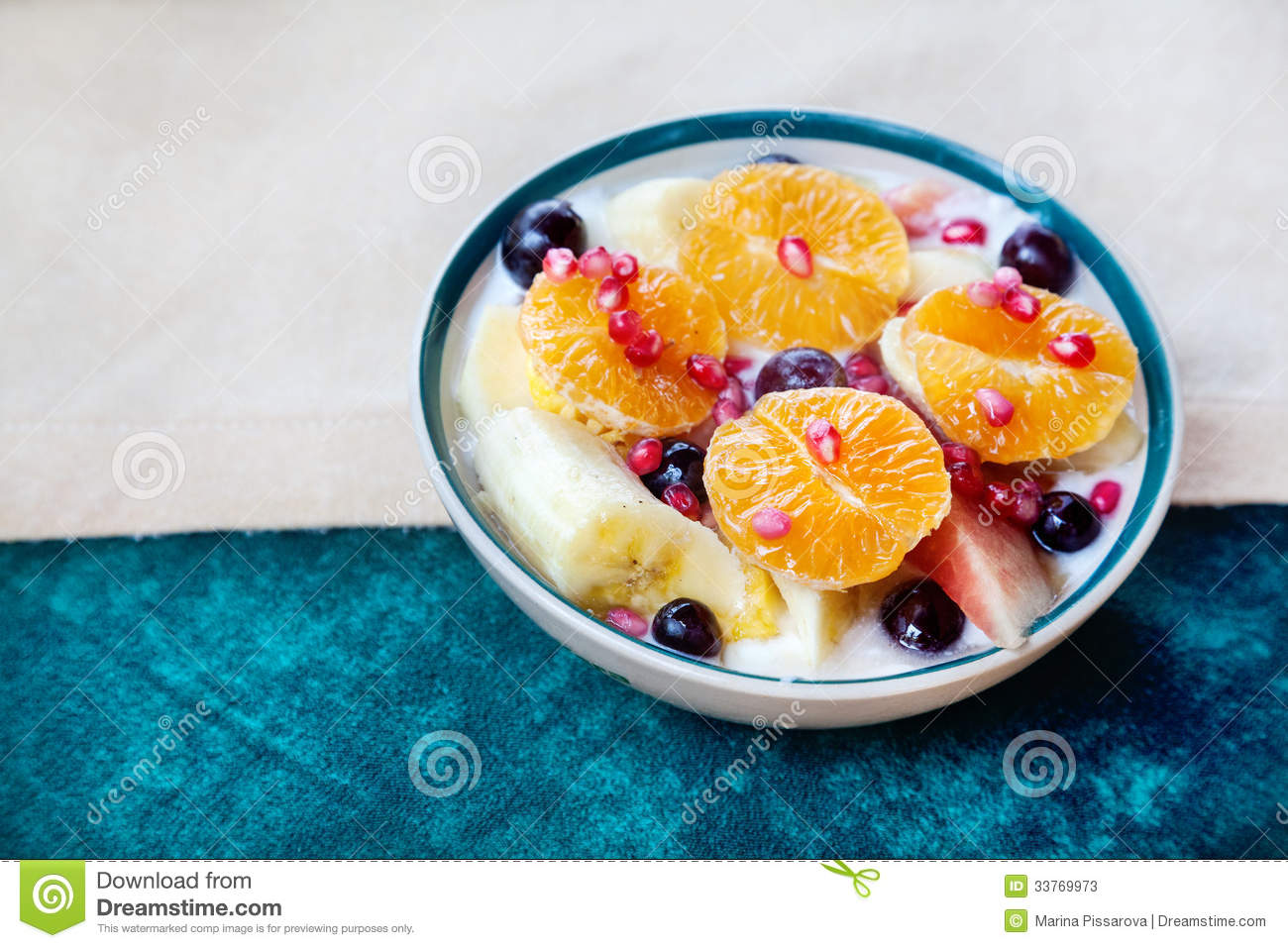 Fruit salad from oranges, bananas, grapes and pomegranate on the table ...