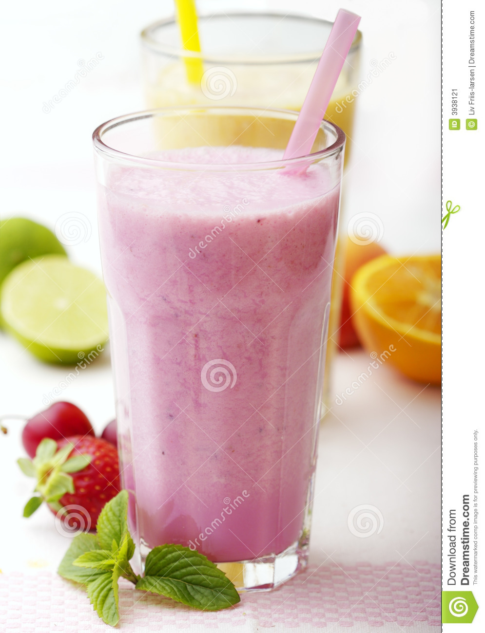 Mixed fruit smoothies surrounded by fresh fruit.