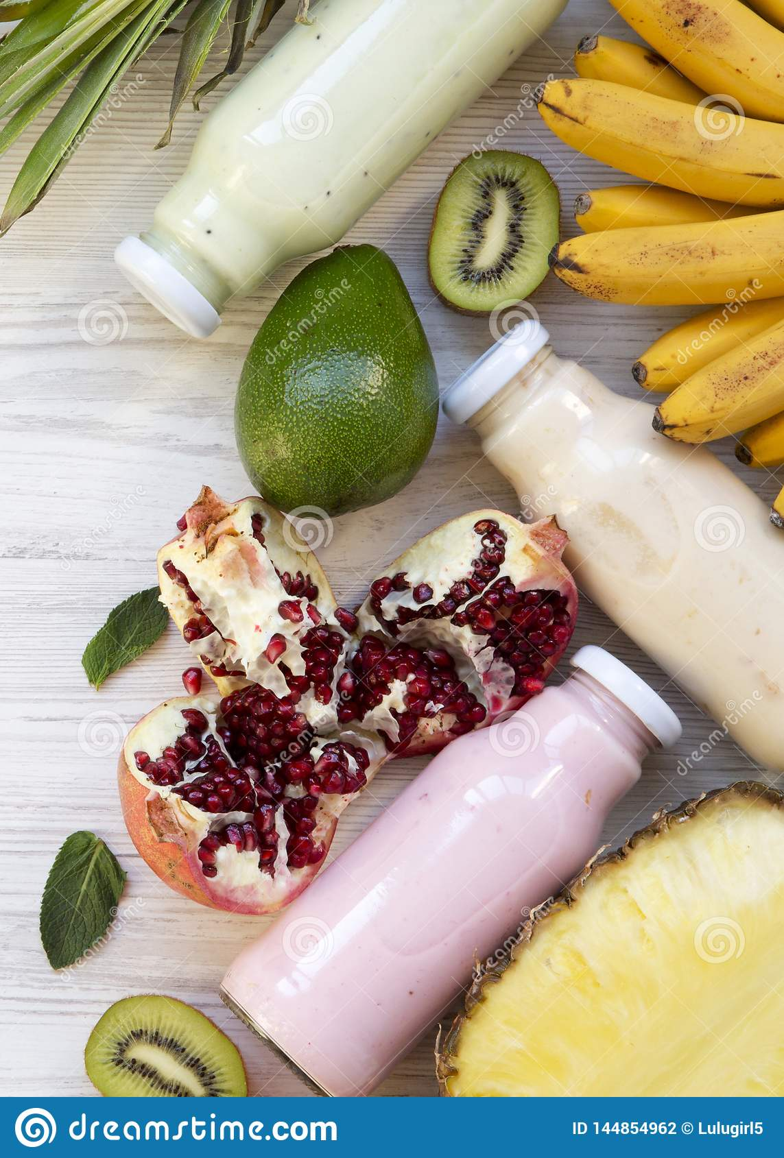 Fruit smoothies or milkshake of various colors in glass jars with colorful fruits on white wooden background, top view. From above