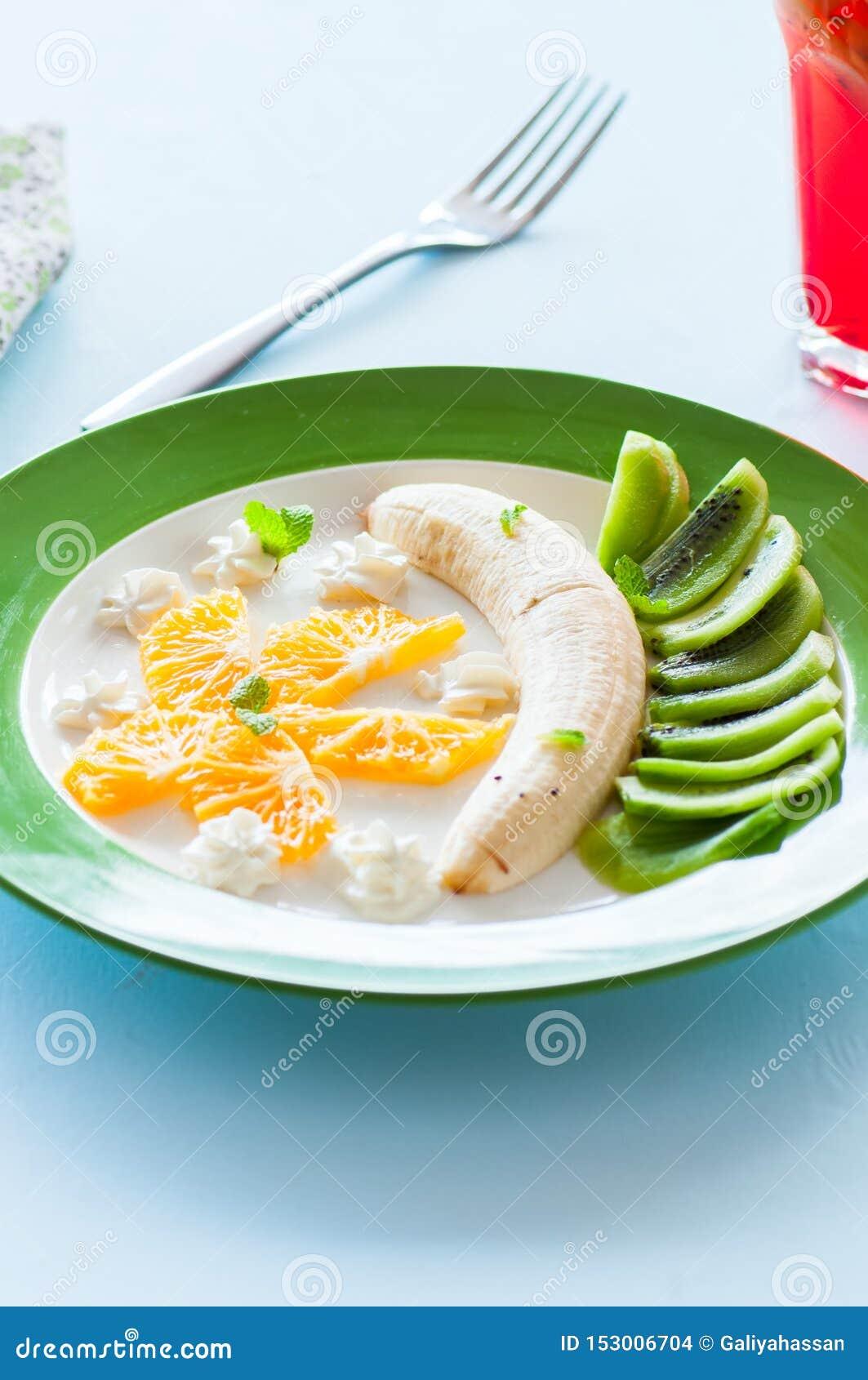 Fruit snack meal for children. Banana, kiwi and orange slices.