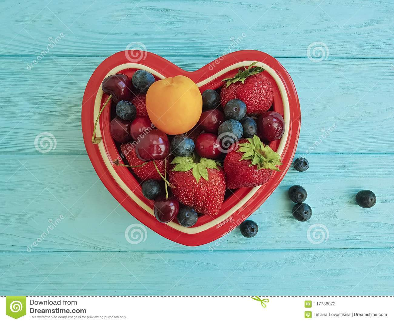 fruit strawberry, blueberry, cherry, apricot detox plate heart on blue wooden