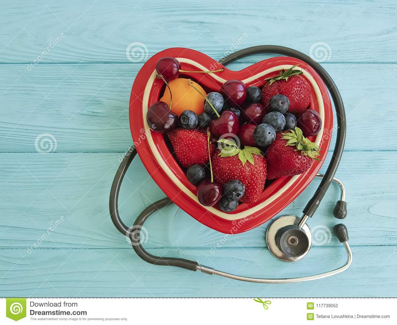 Fruit strawberry, blueberry, cherry, apricot plate heart on blue wooden stethoscope sweet antioxidant mixed