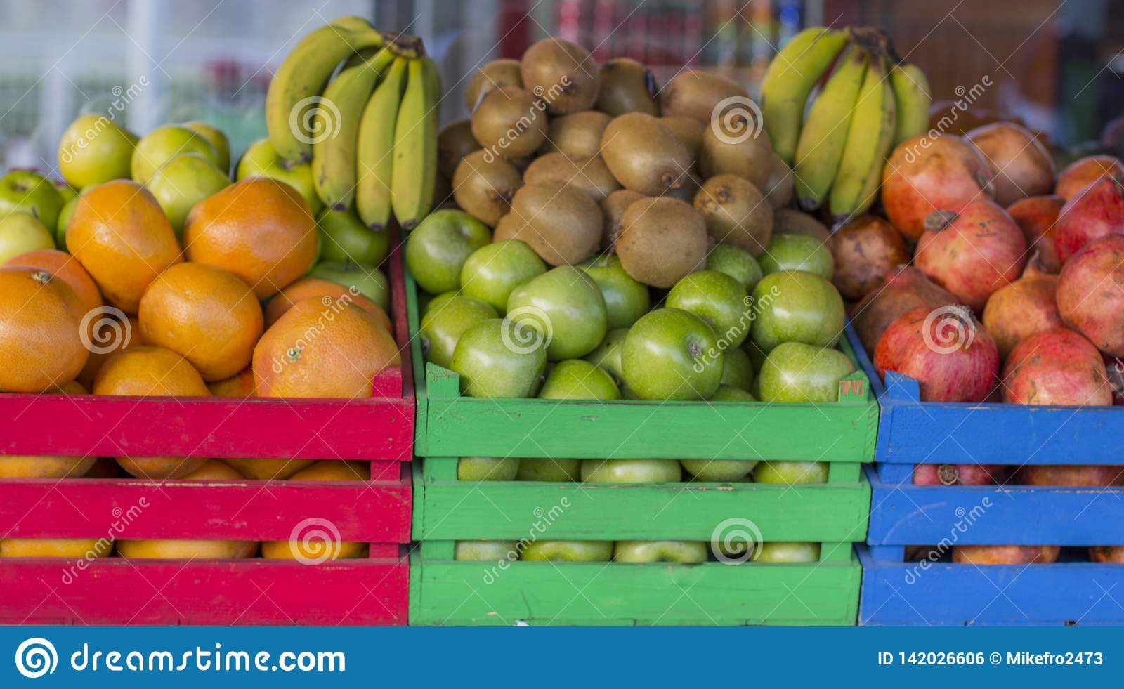 Fruits in colored wooden crates. Cages full of fruit
