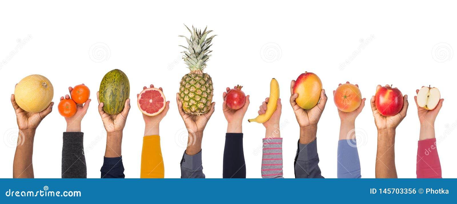 Fruits frais dans des mains d isolement sur le fond blanc