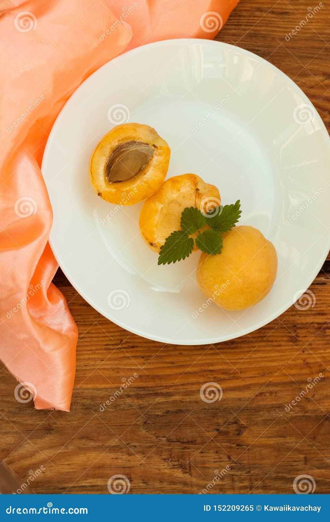 Fruits frais mûrs d abricot d un plat blanc sur le fond en bois L espace de copie, nourriture saine delisious