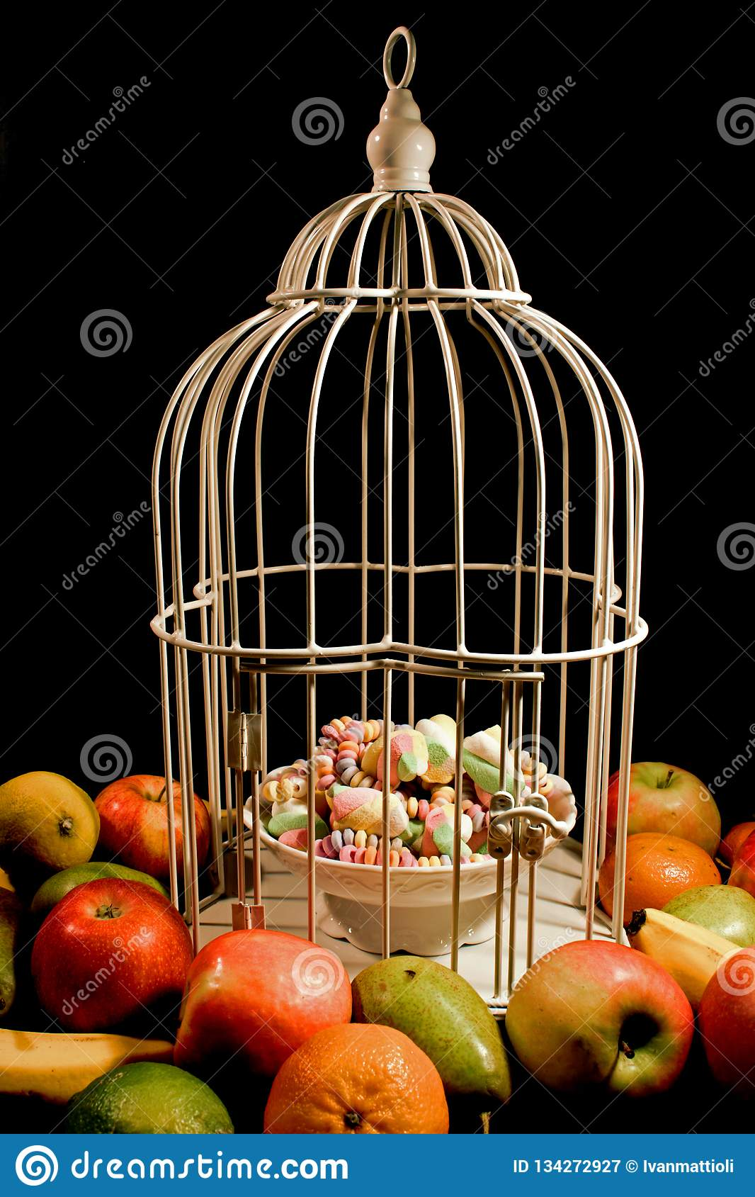 Fruits surrounding a cage with sweets enclosed