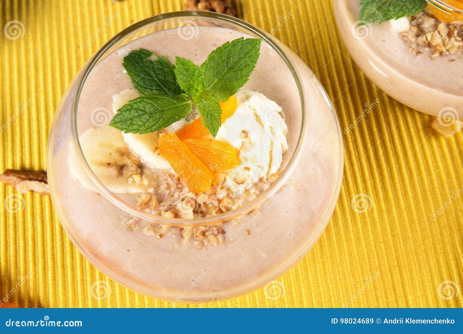 Fruity smoothie w deserowym szkle na żółtym tle Koktajle z wysuszonymi morelami, lody i bananami, odgórny widok