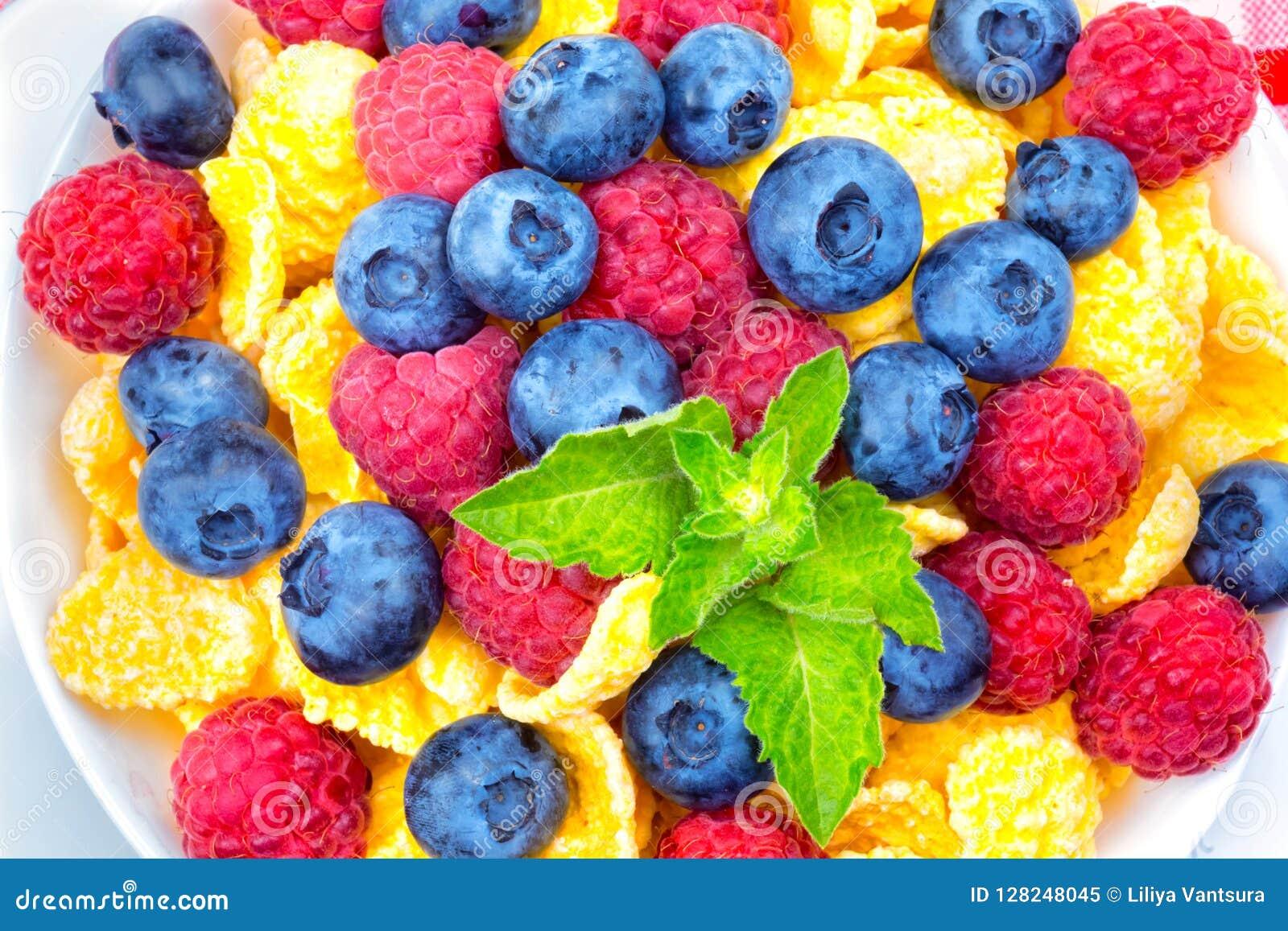 Frukost av cornflakes och bär, hallon, blåbär,