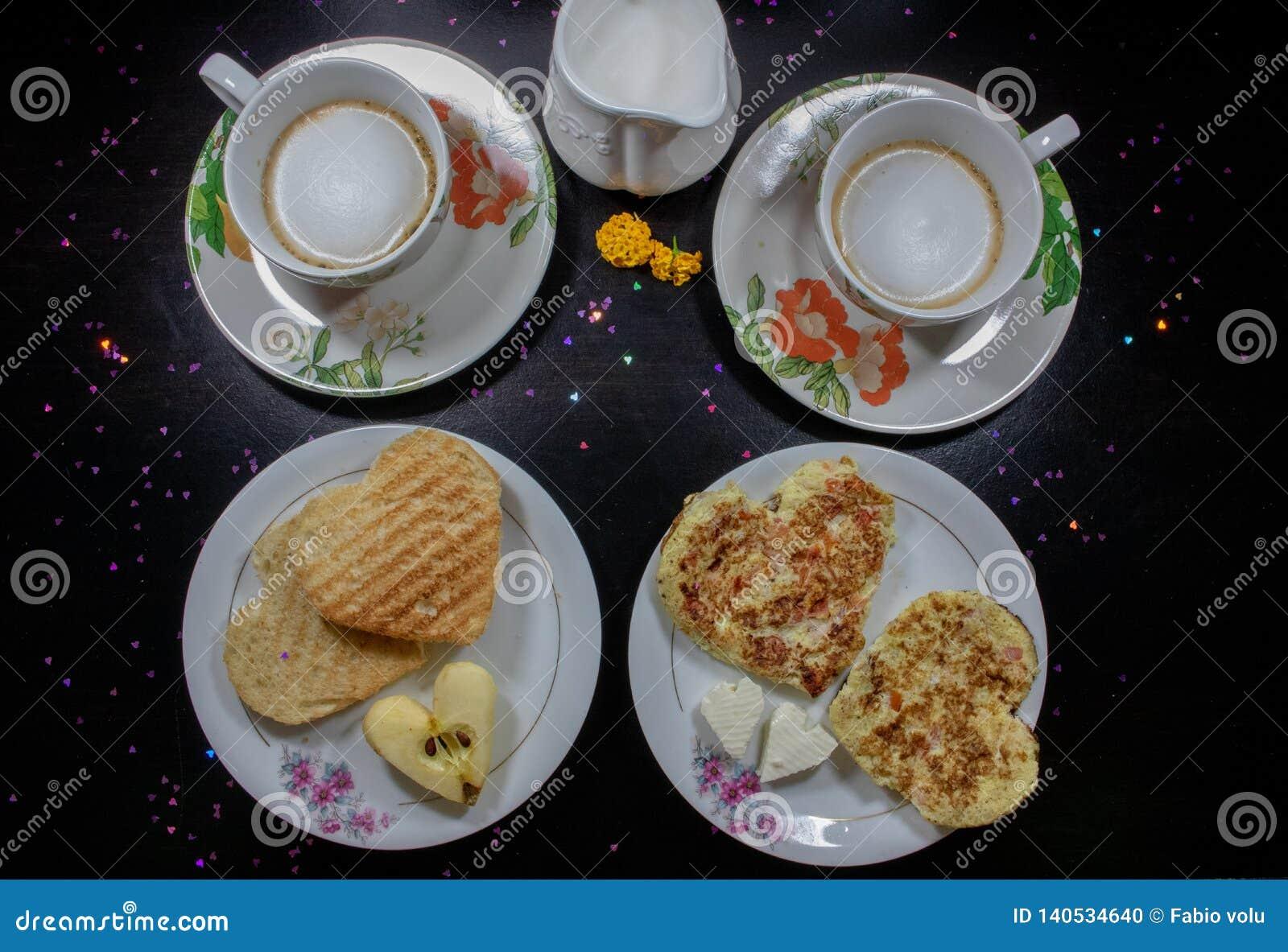 Frukost på valentin dag - stekt omelete, bröd, äpple och vit ost i formen av en hjärtacoffe och att mjölka Top beskådar