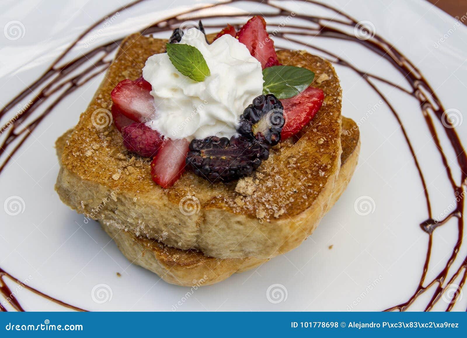 Frukosten för franskt rostat bröd tjänade som med bär, mintkaramellen och kräm på en choklad dekorerad vit platta