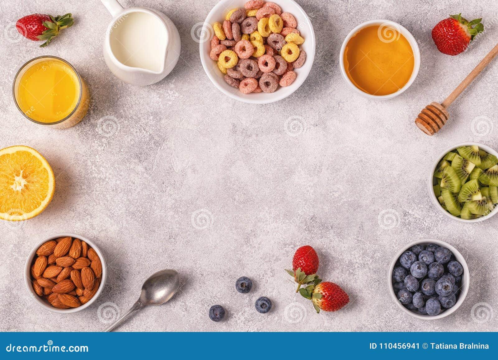 Frukosten med färgrika sädesslagcirklar, frukt, mjölkar, fruktsaft