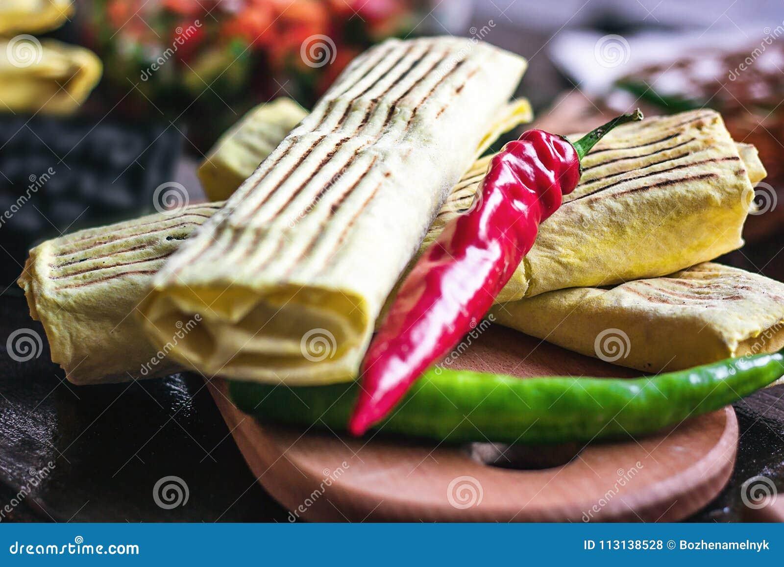 Frukostera den mexikanska snabbmatmatställen för två kryddiga läckra burritos på den wood tabellen för träbrädet som dekoreras me
