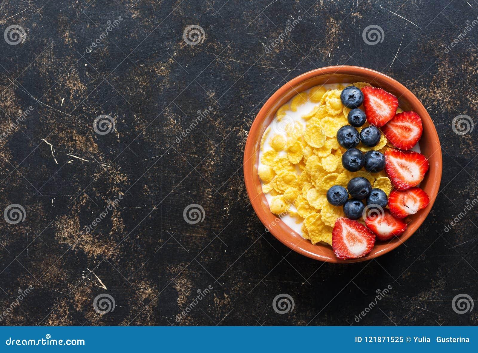 Frukostera havreflingor med mjölkar och nya bär, jordgubbar, blåbär på en mörk bakgrund Bästa sikt, kopieringsutrymme Diet-f