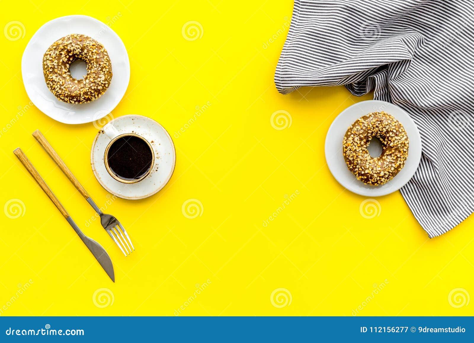 Frukostera med kaffe, donuts och blommor på gul modell för bästa sikt för bakgrund