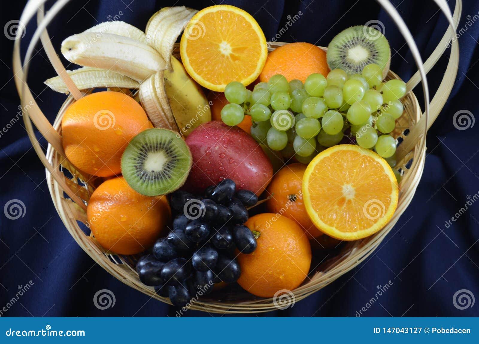 Frukter i en vide- korg på ett mörkt - blå tygbakgrund