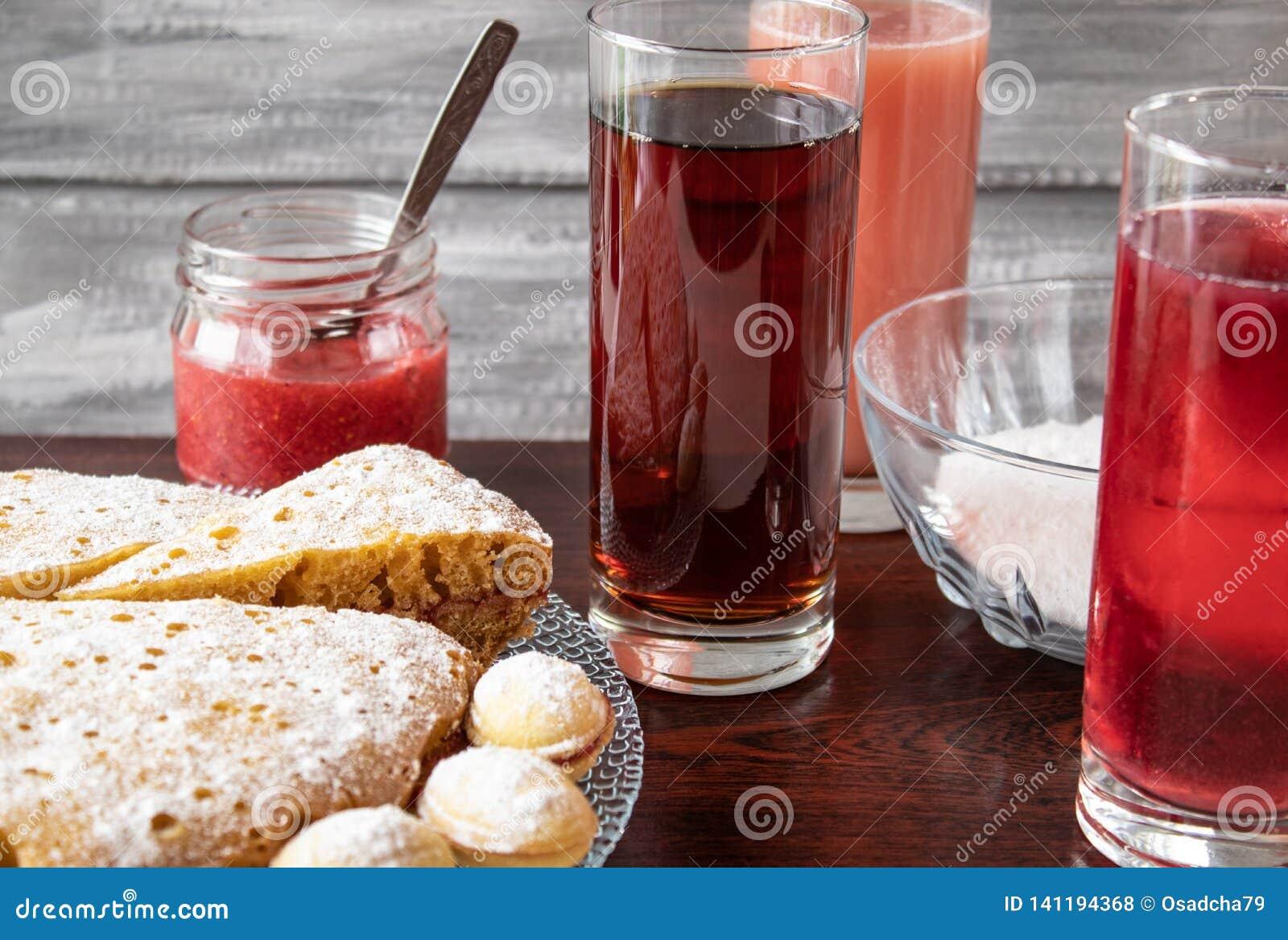 Fruktsaft i ett exponeringsglas i bakgrunden, en paj på en bunke och driftstopp i en liten krus
