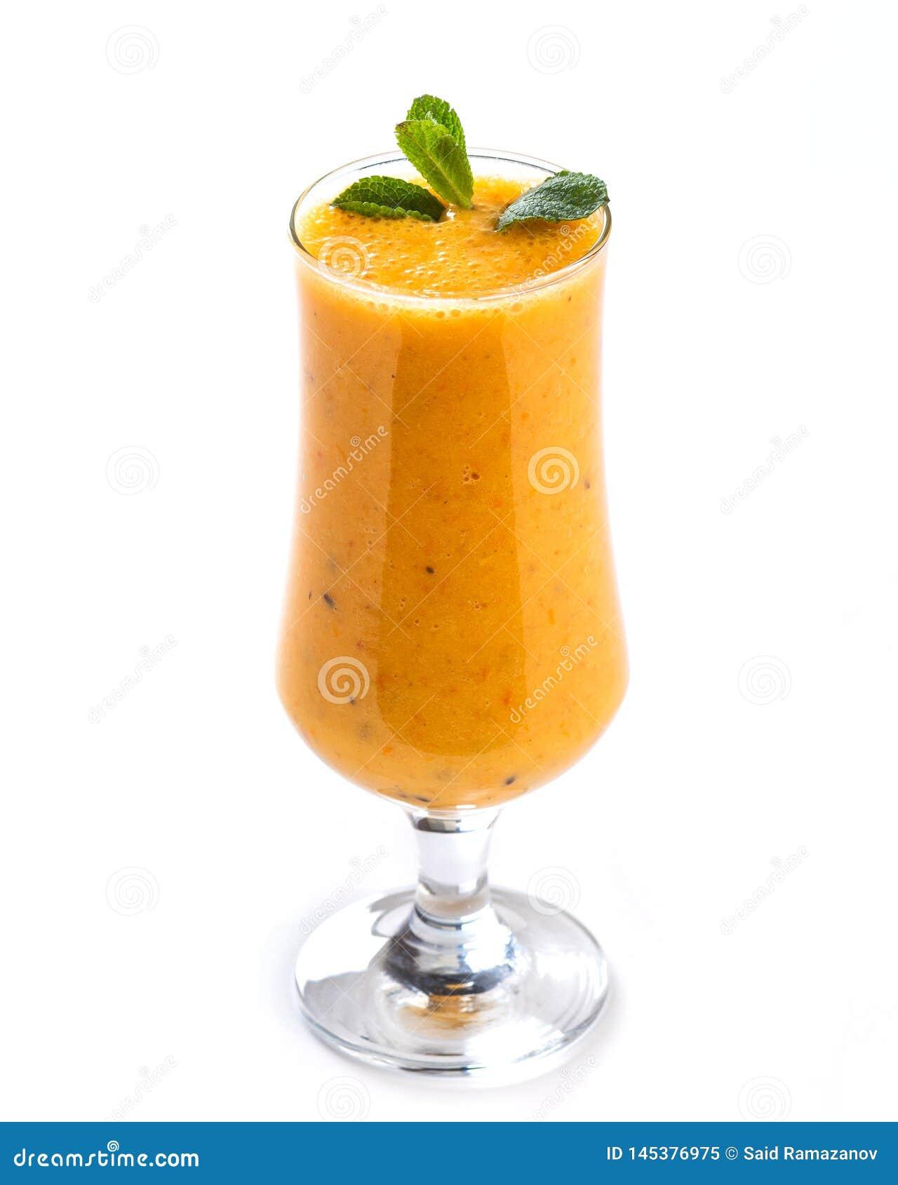 Frullato arancio in un vetro alto decorato con una foglia della menta su fondo bianco isolato