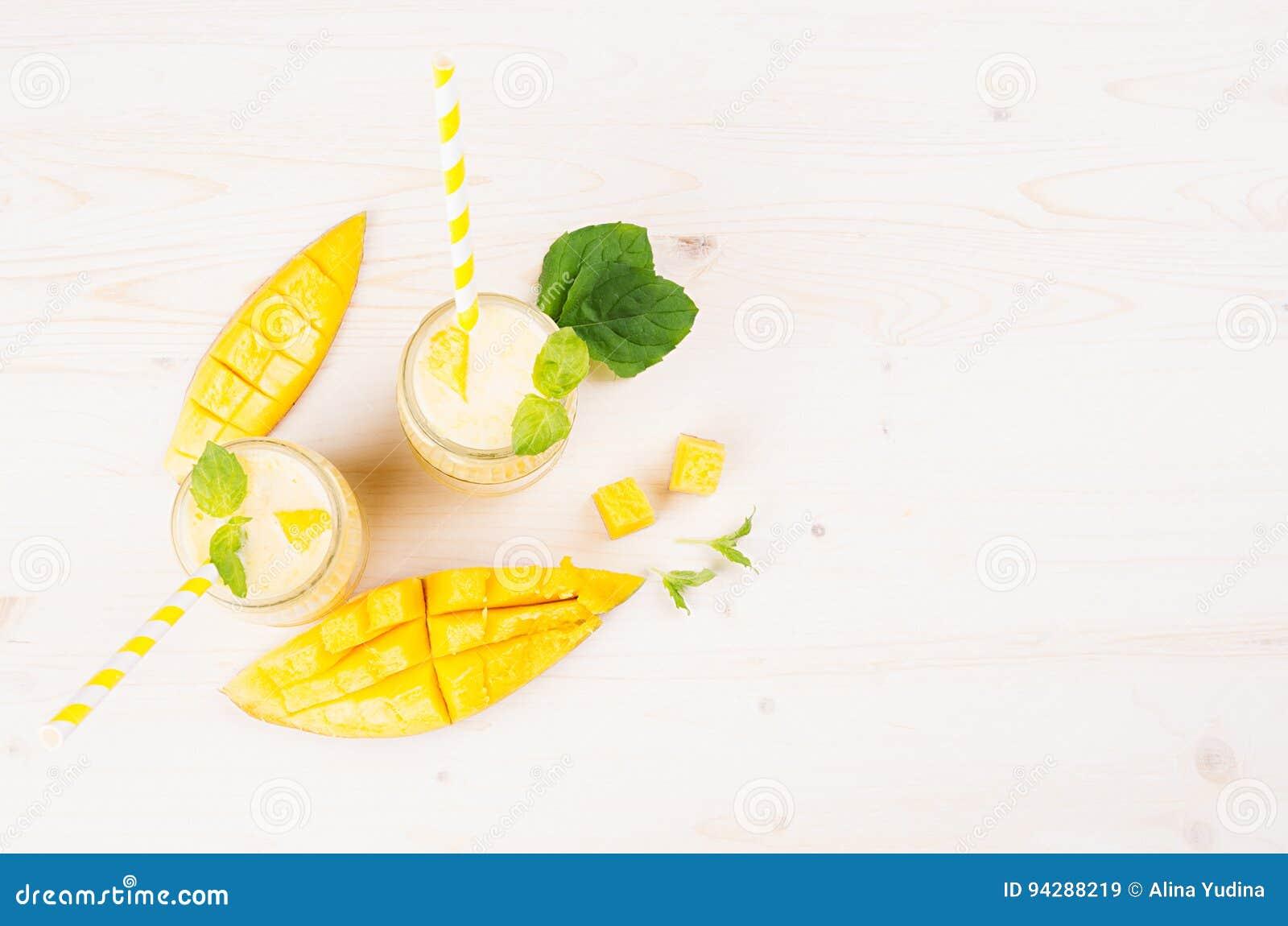 Frullato giallo della frutta del mango in barattoli di vetro con paglia, foglie di menta, fette del mango, vista superiore Fondo