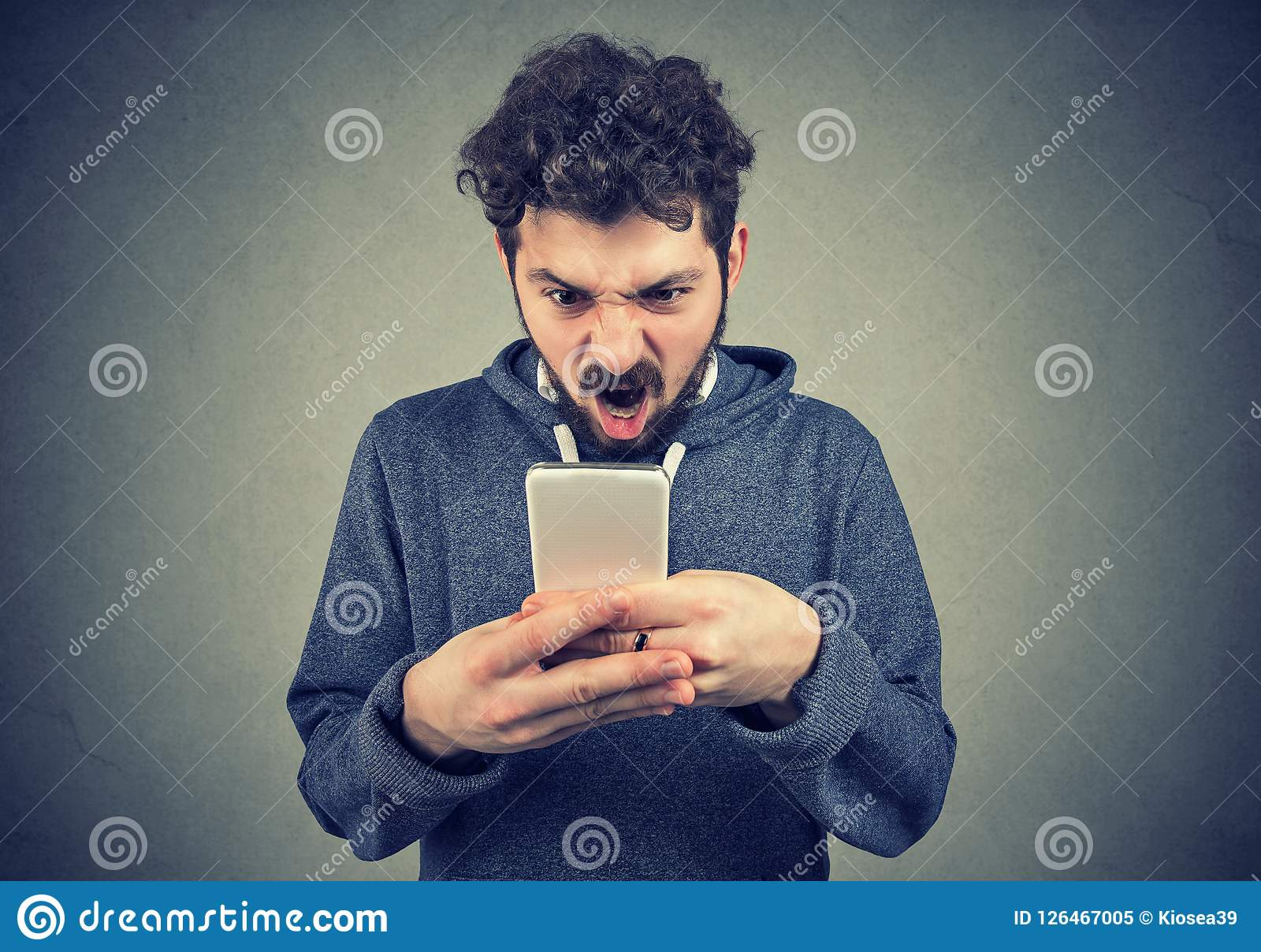 Frustrated angry man reading a text message on his smartphone feeling frustrated