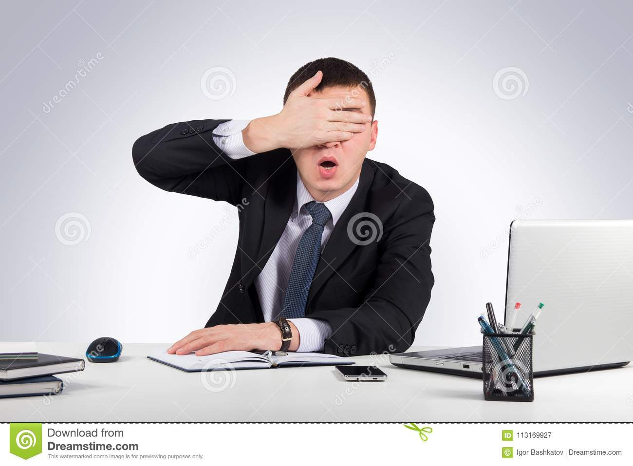 Frustrated businessman close his eyes by hand on gray background