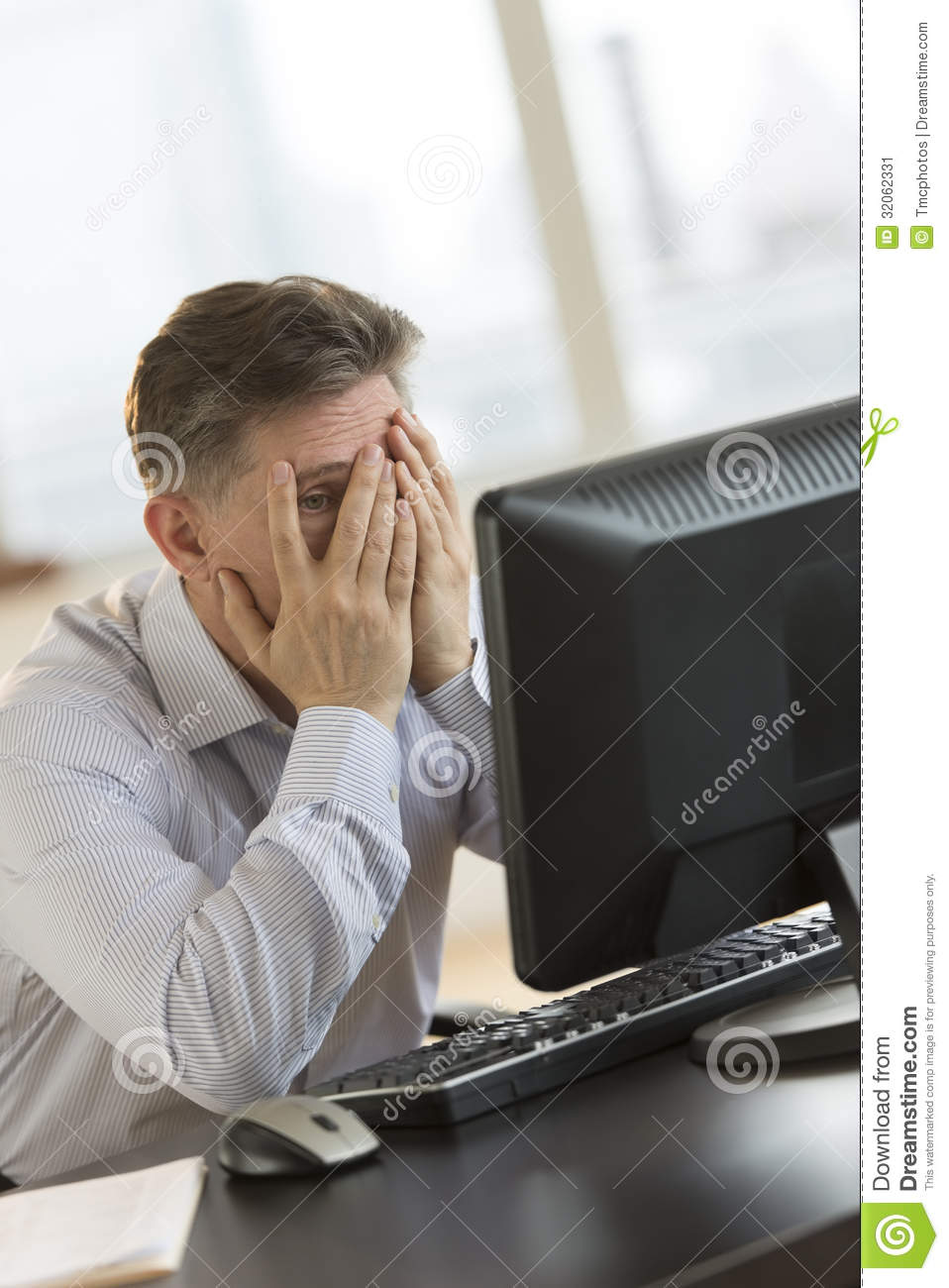 Frustrated Businessman With Hands On Face Looking At