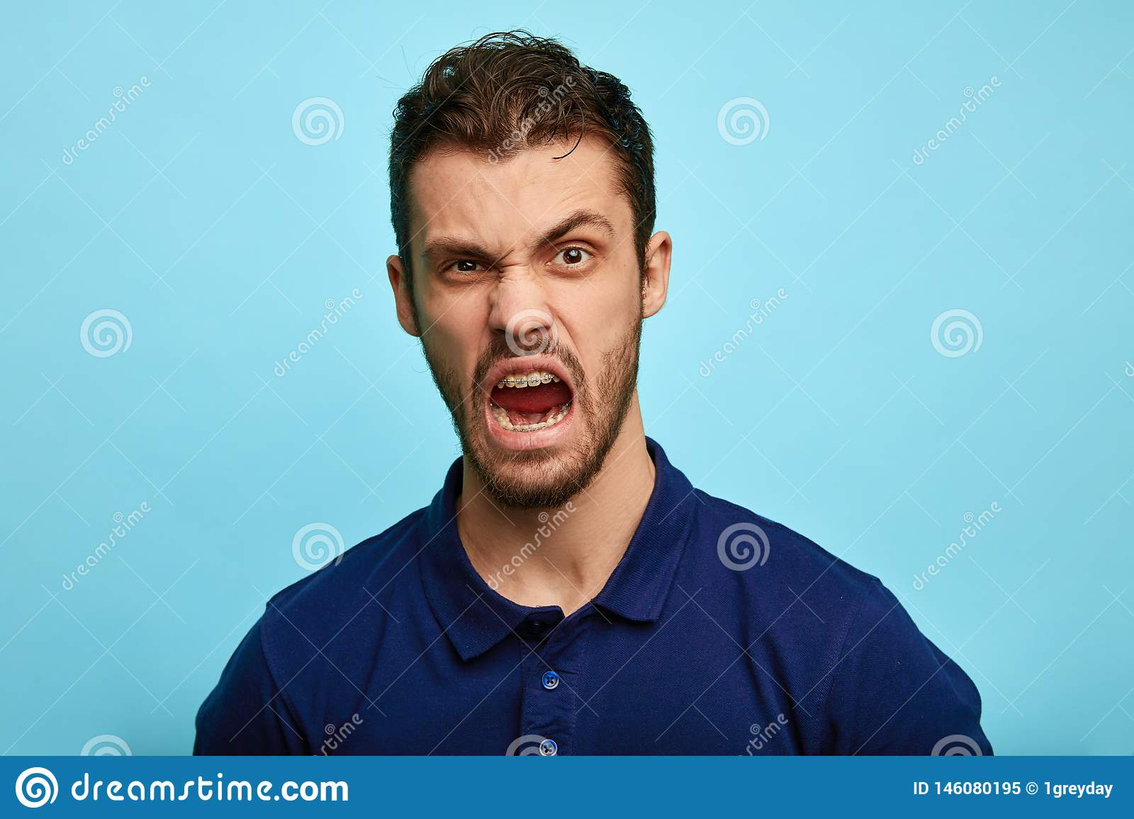 Frustrated, enraged man with grumpy grimace on his face,