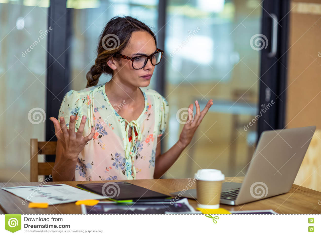 Frustrated female graphic designer looking at laptop