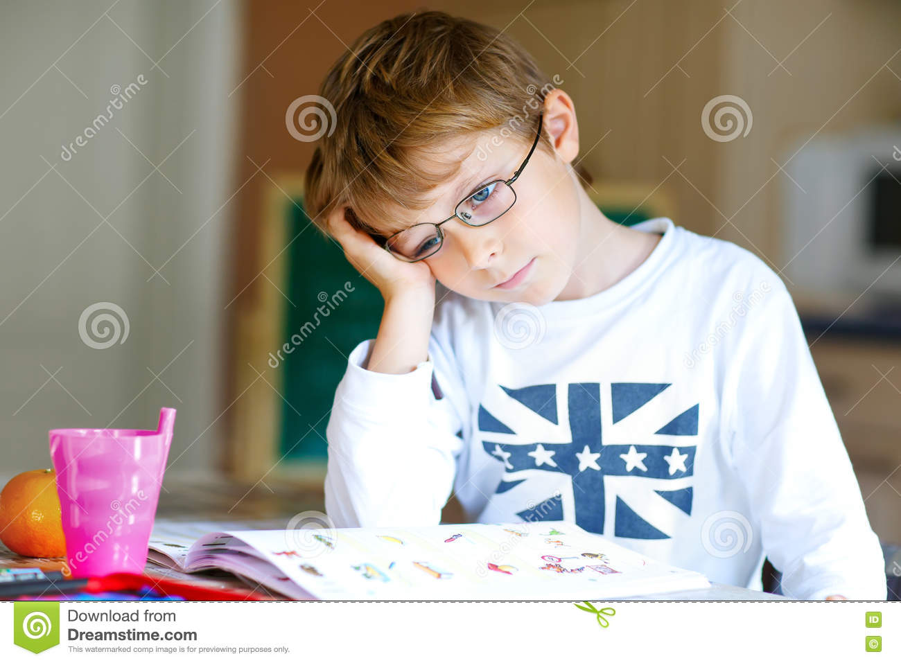 40458f306e6 Portrait of frustrated school kid boy with glasses at home making homework. Little  child writing with colorful pencils