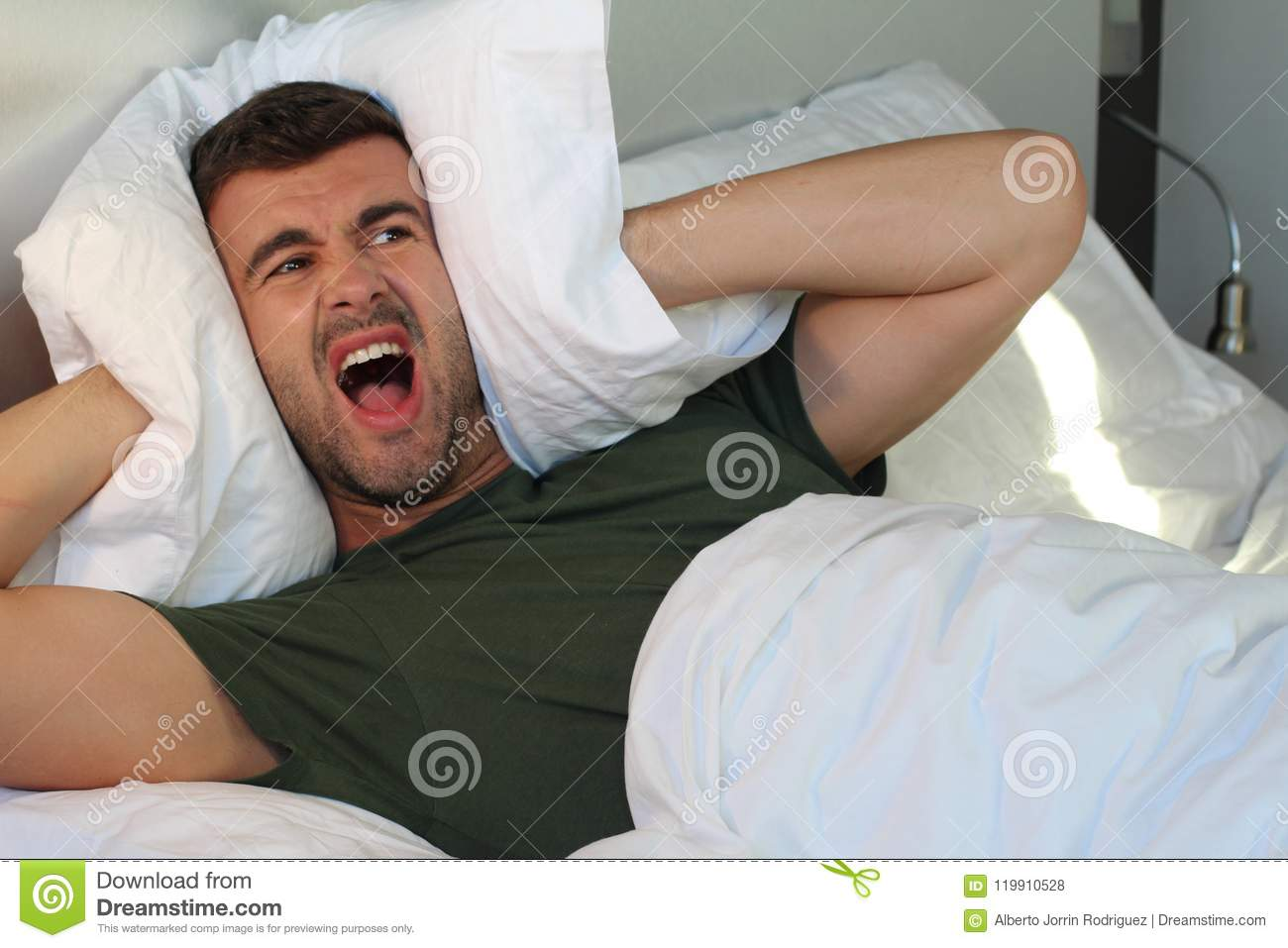 Frustrated man covering his ears with pillow