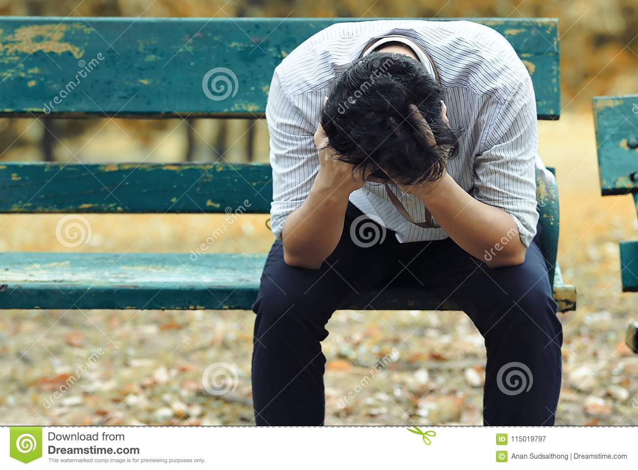 Frustrated stressed Asian business man with hand cover face sitting on the bench of public park and suffering from depression and