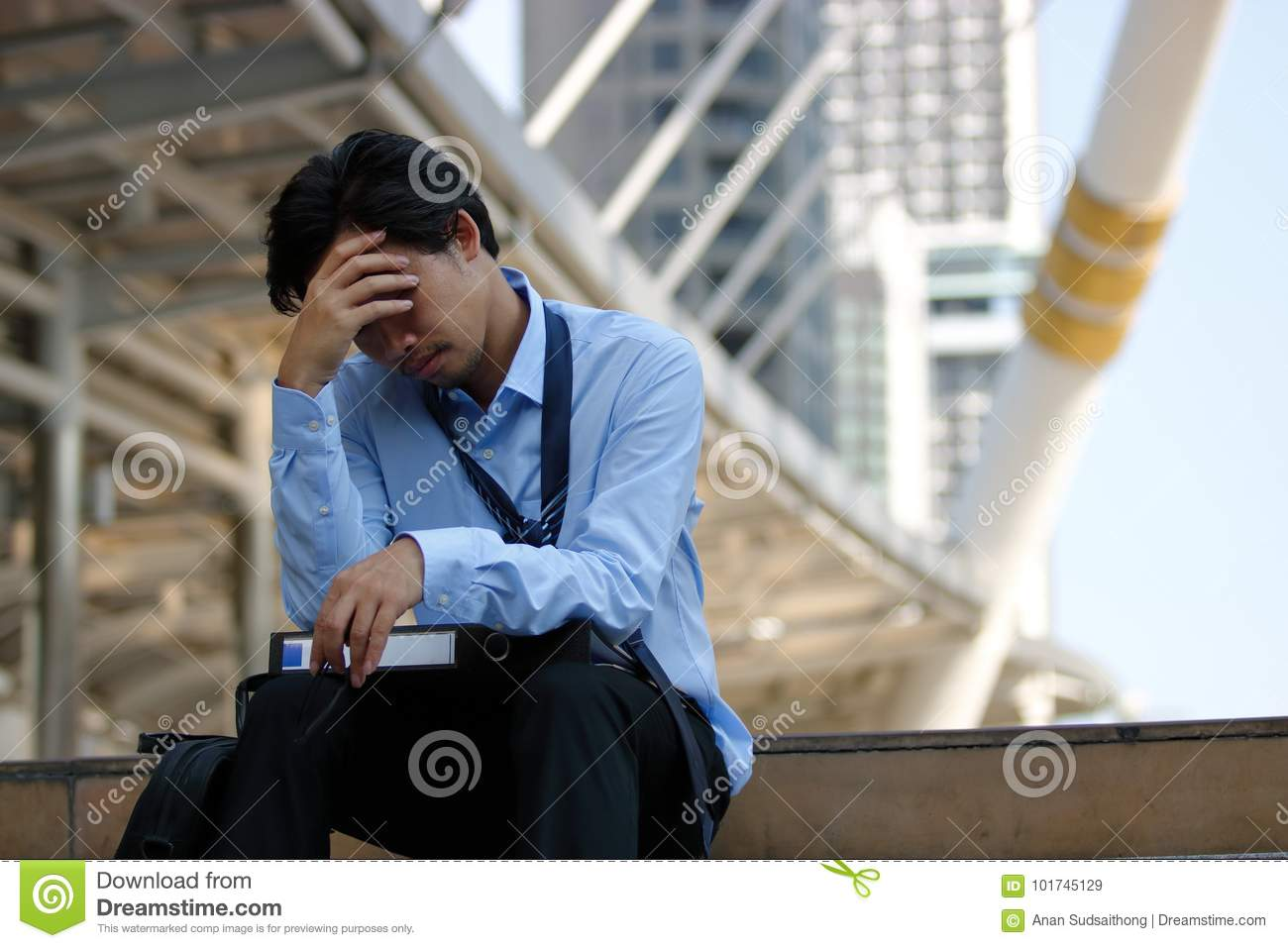 Frustrated stressed Asian businessman with hand on forehead sitting on staircase in the city. Depressed unemployment business conc