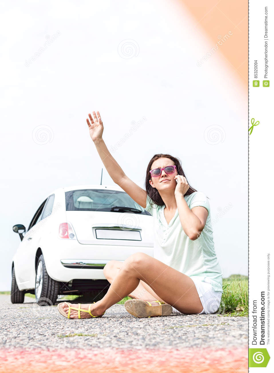 Frustrated woman hitchhiking while using cell phone by broken down car
