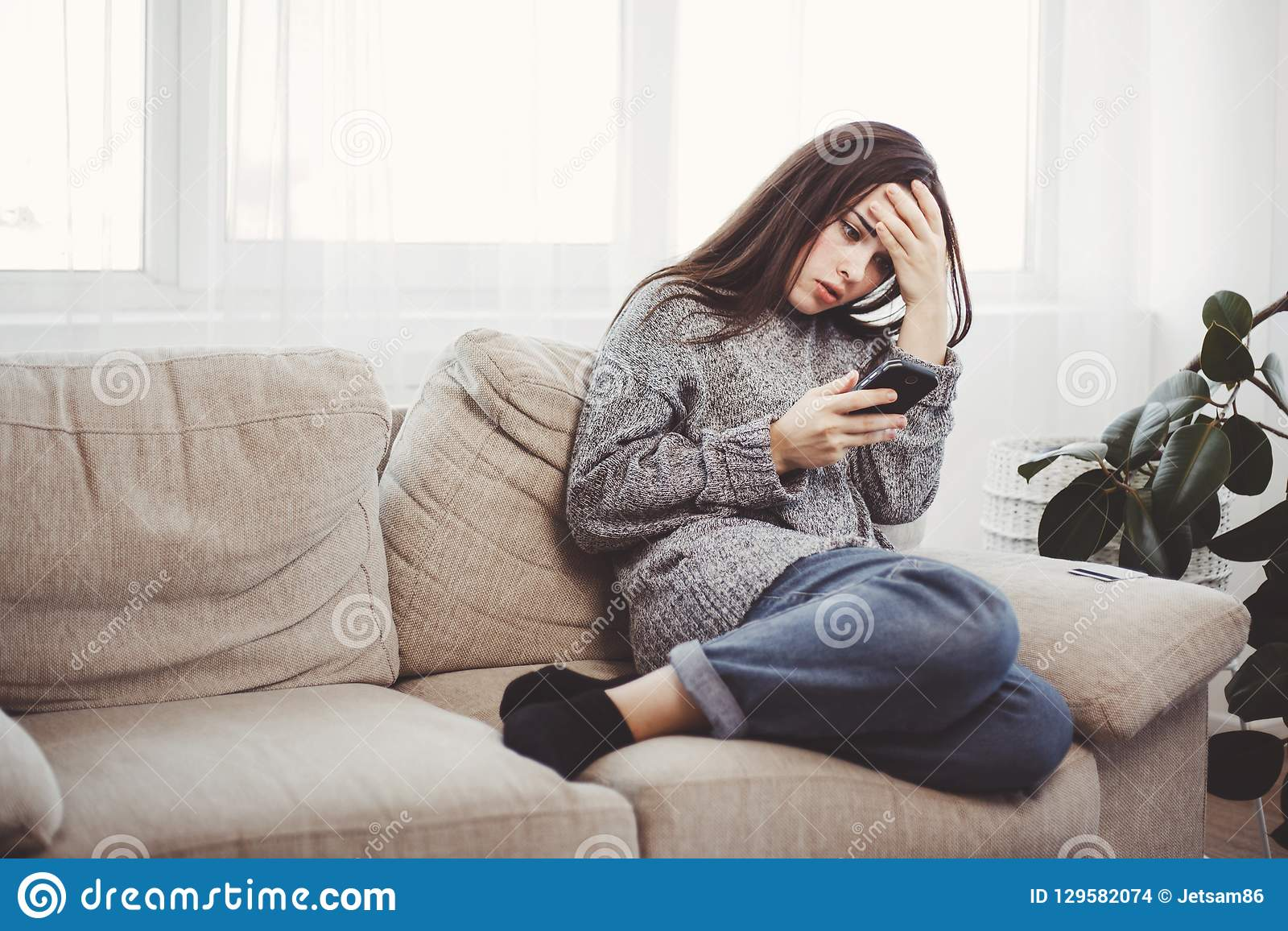 Frustrated woman reading message in a smartphone