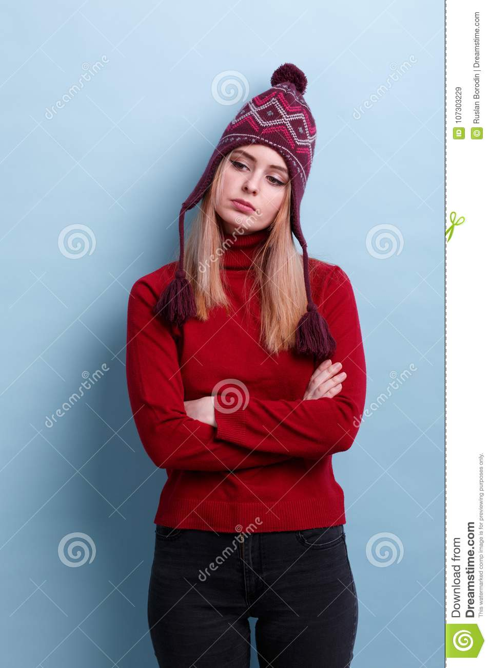 A Frustrated Girl, In A Warm Hat And Sweets, Stands Cross