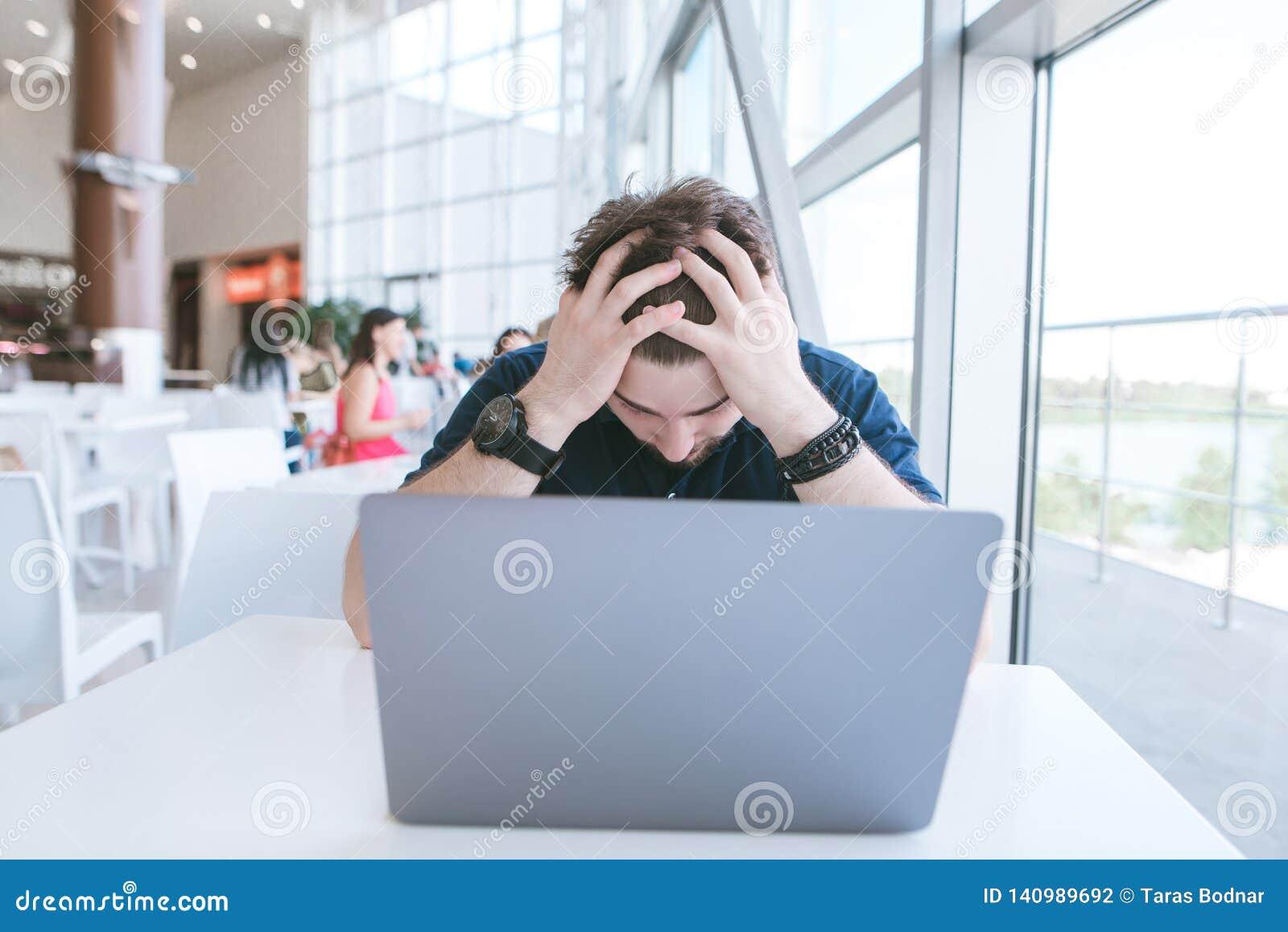 Frustrerad man som arbetar på en bärbar dator i ett kafé Den ledsna affärsmannen har fällt ned hans huvud från fel